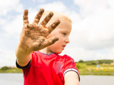 muddy: Child little blonde boy kid playing outdoor showing dirty muddy hands. Happy childhood.