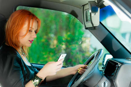 Concept of danger driving. Young woman driver red haired teenage girl texting on cell phone sending text reading message while driving the car.