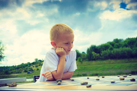 draughts: Draughts board game. Little boy clever child kid playing checkers thinking outdoor in the park. Childhood and development