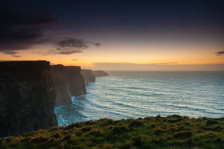 europe: Famous cliffs of Moher at sunset in Co. Clare Ireland Europe. Beautiful landscape natural attraction.