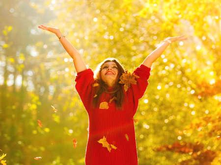 행복은 평온합니다. 여자 가을 공원에서 휴식을 던지고 위로 팔을 제기하는 공기에 나뭇잎. 화려한 숲 단풍 야외에서 아름 다운 소녀입니다.