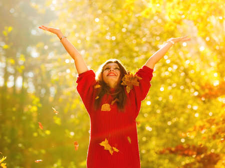 Happiness carefree. woman relaxing in autumn park throwing leaves up in the air with arms raised up. Beautiful girl in colorful forest foliage outdoor. Archivio Fotografico