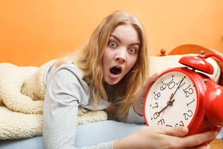 oversleep: Panic woman waking up late in morning turning off alarm clock. Young girl laying in bed.