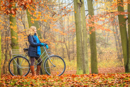 leisure activities: Active woman riding bike bicycle in fall autumn park. Young girl in jacket and scarf relaxing. Healthy lifestyle and recreation leisure activity. Stock Photo