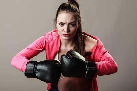 Training, boxing and exercises. Women lifestyle concept. Fit girl with gloves on grey background in studio.