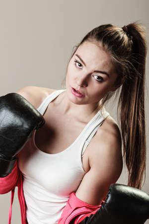 feministische: Feministische en emancipatie idee. Vrouw in mannelijk beroep, opleiding boksen. Fit vrouwelijke fitness meisje doen oefening op een grijze achtergrond. Stockfoto
