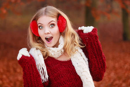 pullover: Portrait of pretty smiling fashionable woman in fall forest park. Happy gorgeous young girl in red earmuffs and sweater pullover. Autumn winter fashion. Stock Photo