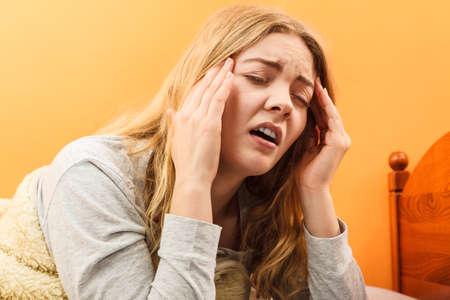 enfermos: Mujer enferma que sufre de dolor de cabeza. Muchacha enferma por la que se en la cama cogi� fr�o. Foto de archivo