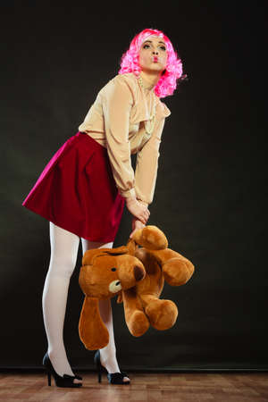 puppet woman: Mental disorder concept. Young childlike woman wearing like puppet doll and big dog toy standing dark black background