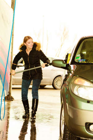 dirty car: Auto wash. Young attractive blonde woman washing the dirty car on open air Stock Photo