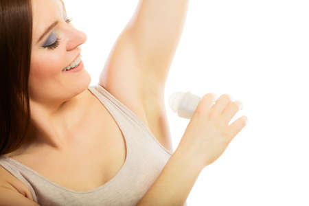 axila: El cuidado diario de la piel y la higiene. Chica aplicar stick desodorante en la axila. Mujer joven que pone desodorante en las axilas en blanco