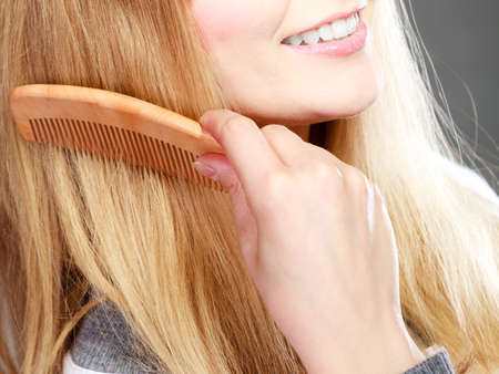 combing hair: Fashion beauty and haircare concept. Closeup blonde woman refreshing her hairstyle girl combing hair with wooden comb gray background Stock Photo