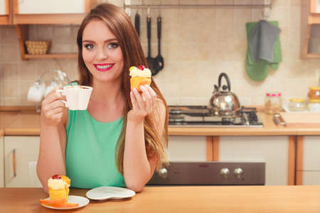 gourmet kitchen: Woman drinking coffee and eating delicious gourmet sweet cream cake. Glutton girl sitting in kitchen with hot beverage and cupcake. Appetite and gluttony concept.