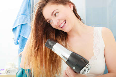 blow dryer: Haircare. Beautiful long haired woman drying hair in bathroom Stock Photo
