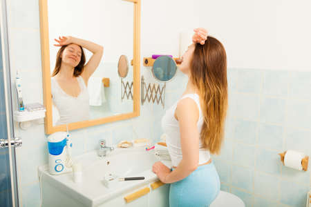 purity: Young girl woman without makeup relaxing in bathroom looking in mirror. Natural beauty. Purity. Stock Photo