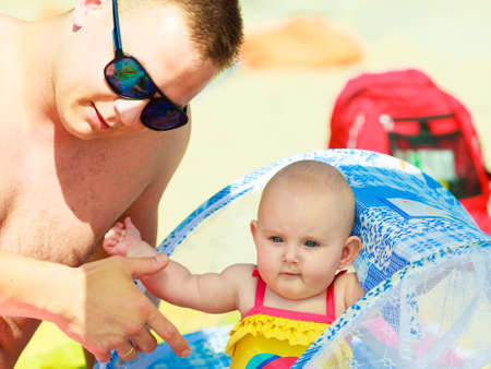 babyhood: Closeup of sweet little baby with father parent. Babyhood and parenting. Stock Photo