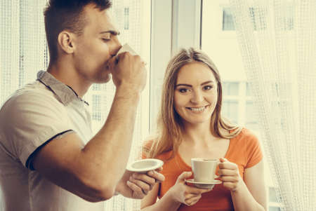 drinking coffee: Happiness and healthy relationship concept. Attractive couple drinking tea or coffee together at home, man and woman holding cups with hot beverage at home