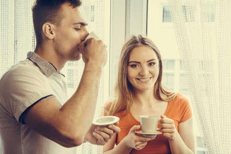 tomando café: La felicidad y el concepto de sana relación. Atractiva pareja beber té o café juntos en casa, el hombre y la mujer la celebración de copas con bebida caliente en el país Foto de archivo