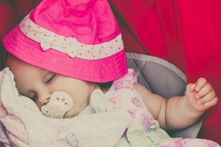 babyhood: Closeup of sweet little baby covered with pink hat. Babyhood.   Stock Photo