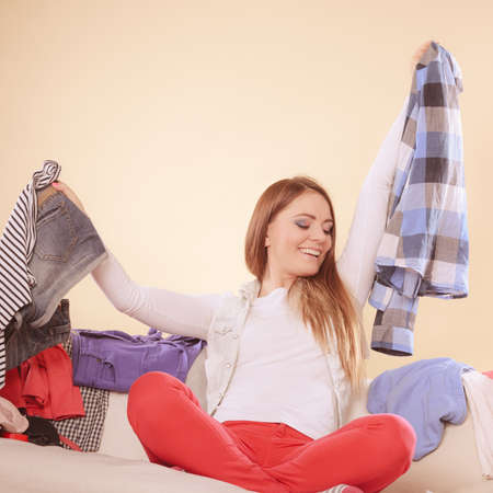 messy room: Happy woman sitting on sofa couch in messy living room holding clothes. Young girl surrounded by many stack of clothing. Disorder and mess at home.