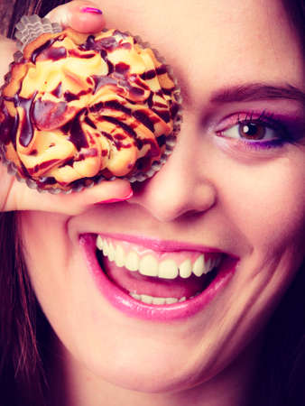 cupcakes: Diet sweet food and people concept. Funny woman holds cake in hand having fun covering her eye with cupcake orange background
