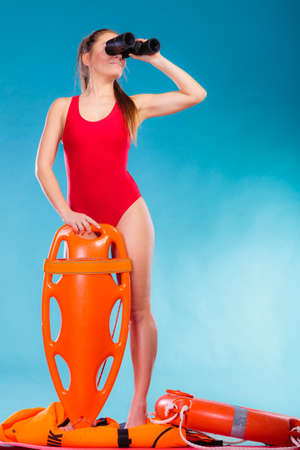 lifesaving: Accident prevention and water rescue. Attractive female model in lifeguard outfit on duty looking through binocular keeping float lifesaver equipment on blue