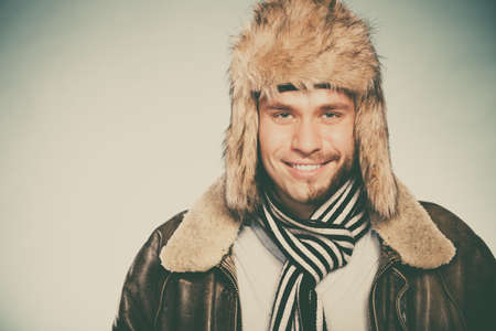 instagram: Portrait of happy man with half shaved face beard hair in fur hat and scarf. Smiling handsome guy on blue. Skin care hygiene and winter fashion. Instagram filter.