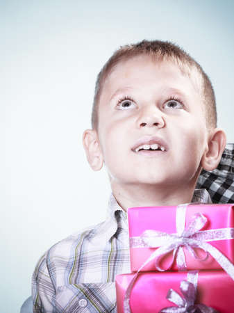 daydream: Happy childhood, holidays christmas time. Little boy child with pink presents gift boxes loking up. Positive emotion.