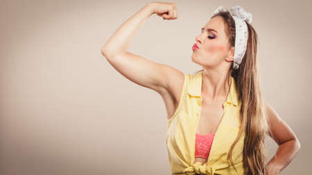 hairband: Happy strong pretty pin up girl with hairband bow showing off muscles. Young gorgeous retro woman in studio.
