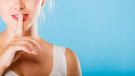 Calme, le secret et le concept de la confiance. Femme main avec signe symbole de silence sur fond bleu. Studio, coup.