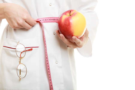 waist down: Slim down dieting concept. woman in white lab coat recommending healthy food. Doctor specialist dietitian holding fruit apple measuring her waist isolated. Stock Photo