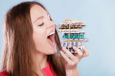 Woman taking pills. Girl female eating stack of tablets. Drug addict and health care concept. Overdose. Stock Photo