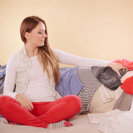 messy clothes: Woman sitting on sofa couch in messy room. Girl surrounded by stack of clothes. Disorder and mess at home.