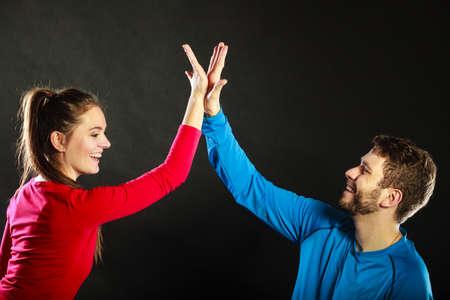 gente exitosa: Hombre y mujer dando de alta cinco. Sonriendo par de amigos que celebran el logro del éxito en el estudio sobre negro. Foto de archivo