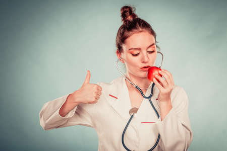 eating right: Happy dietitian nutritionist holding apple with thumb up gesture. Woman promoting healthy food fruit. Right eating nutrition and slimming concept.