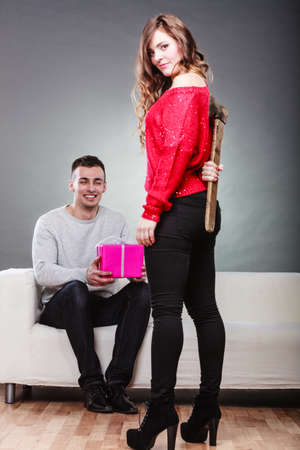axe girl: False feelings, relations problem. Trusting guy giving present pink box to misleading girl. Insincere woman holding axe behind her back Stock Photo