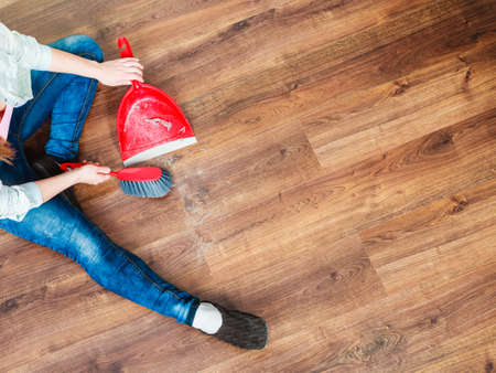 Cleanup housework concept. cleaning woman sweeping wooden floor with red small whisk broom and dustpan unusual high angle view
