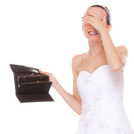 expenditure: Worried bride with empty wallet grabbing her head. Young girl holding purse looking for money cash. Wedding expenses costs, expenditure. Finance concept. Woman in white wedding dress isolated on white background.