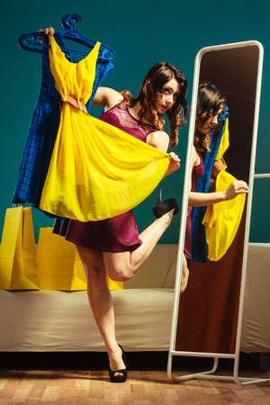 espejo: Moda y compras. Mujer que se prepara para partido, tratando vestido elegir la ropa. Atractiva mujer joven comprador busca en el espejo, de pie en la tienda de ropa.