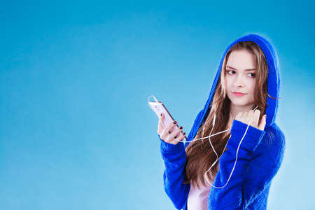 listening: young woman with smart phone listening music. Teen stylish long hair girl in hood relaxing or learning language. Studio shot on blue.