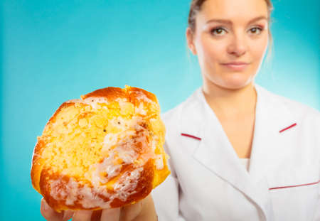 recommending: Unhealthy nutrition overweight concept. Nutritionist saying no to sugary dessert. Woman doctor dietician holding sweet bun recommending non sugar diet on blue