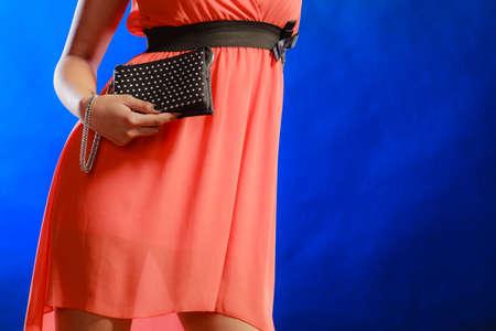 clutch bag: Fashion elegant evening outfit. Female hand holding black rivet leather handbag clutch bag on blue background Stock Photo