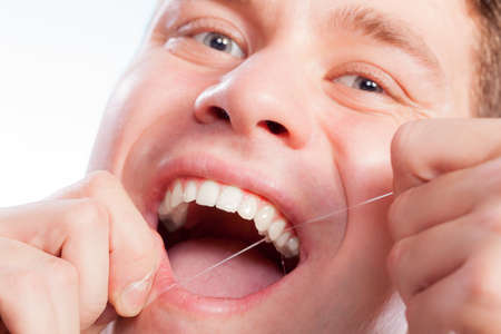 flossing: Daily health care. Young man cleaning flossing his white teeth with dental floss Stock Photo