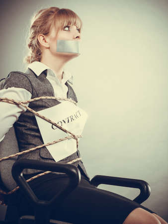 taped: Afraid businesswoman bound by contract terms and conditions with mouth taped shut. Scared woman tied to chair become slave. Business and law concept. filtered.