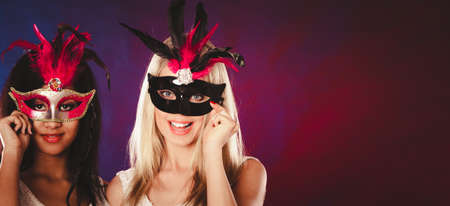 masquerade mask: Holidays, people and celebration concept. two women mixed race and caucasian with carnival venetian masks over festive background.