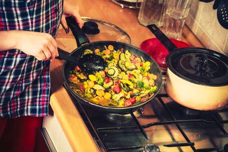 alimentos congelados: Primer plano de humano en cocina cocina revuelva freír las verduras congeladas. Persona freír hacer comida deliciosa cena comida.