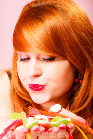 red haired woman: Candy addiction. Multi colored jelly sweets in red haired woman hands. Studio shot.