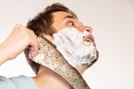 machete: Scared cautious young man with shaving cream foam having fun with machete large knife. Handsome guy removing face beard hair. Skin care and hygiene humor.