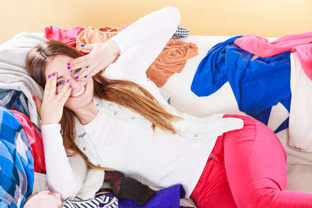 disorganized: Portrait of happy glad young woman girl lying on stack of clothes covering eyes. Disorder and mess.