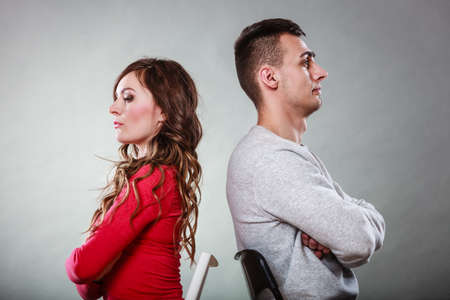 personas discutiendo: Mala relación de conceptos. Hombre y mujer en desacuerdo. Joven pareja después de la pelea sentado en sillas de espalda con espalda